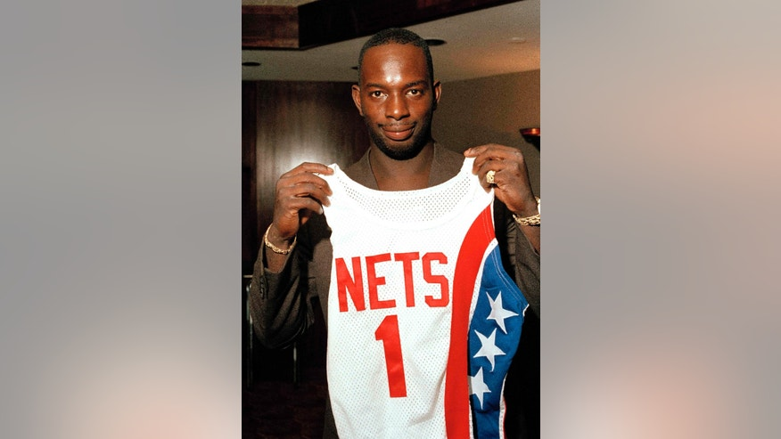 """Aug. 20, 1986: Dwayne """"Pearl"""" Washington, the first draft pick by the New Jersey Nets, holds up his new uniform during a press luncheon at the Meadowlands Arena in East Rutherford, N.J."""