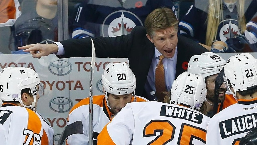 FILE - In this Nov. 7, 2015, file photo, Philadelphia Flyers head coach Dave Hakstol,top, speaks to his players during the first period of NHL hockey game against the Winnipeg Jets in Winnipeg, Manitoba. Last summer Hakstol became the first college hockey coach to get hired by an NHL team in almost 30 years. His success in his first season with the Flyers almost certainly means it won't be another 30 years until the next one. (John Woods/The Canadian Press via AP, File)