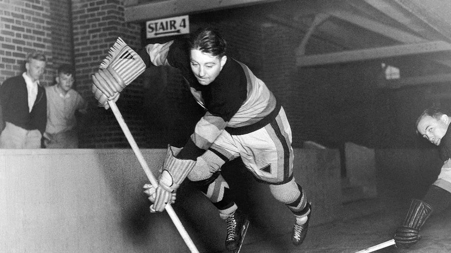 FILE - In this Oct. 24, 1935, file photo, Chicago Blackhawks' Tommy Cook is shown in a posed action as he gets trim for the NHL hockey season in Chicago. Hockey sticks used to come one size fits all. If a player wanted a stick to have a better fit, it required lots of do it yourself, cutting, heating and bending it into a shape and size that fit. That changed with the introduction of composite sticks. Now players get their sticks already custom fit, with precise specifications on everything from the curve of the blade to the shape of the shape of the shaft ready to go right out of the box. (AP Photo/File)
