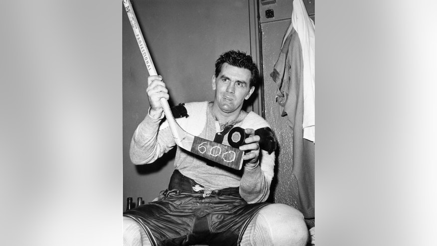 "FILE - In this Nov. 26, 1958, file photo, Montreal Canadiens' Maurice ""the Rocket"" Richard poses with his hockey stick marked 600 and a puck after scoring his 600th career goal in an NHL hockey game against New York Rangers in New York. Hockey sticks used to come one size fits all. If a player wanted a stick to have a better fit, it required lots of do it yourself, cutting, heating and bending it into a shape and size that fit. That changed with the introduction of composite sticks. Now players get their sticks already custom fit, with precise specifications on everything from the curve of the blade to the shape of the shape of the shaft ready to go right out of the box. (AP Photo/File)"