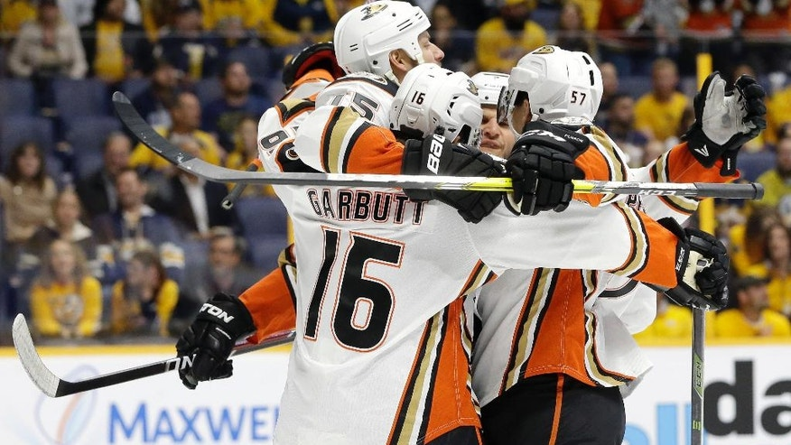 Anaheim Ducks center Ryan Getzlaf, top left, celebrates with Ryan Garbutt (16) and David Perron (57) after Getzlaf scored a goal against the Nashville Predators during the first period of Game 4 in an NHL hockey first-round Stanley Cup playoff series Thursday, April 21, 2016, in Nashville, Tenn. (AP Photo/Mark Humphrey)