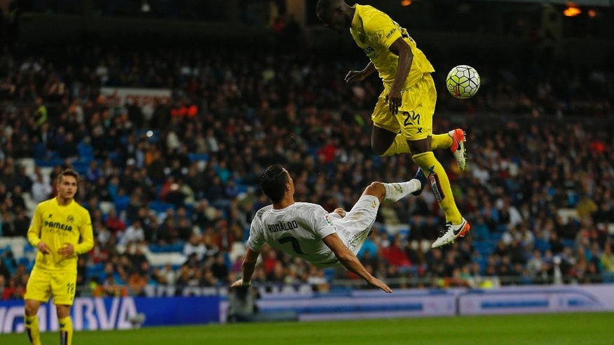 Real Madrid's Cristiano Ronaldo, center, attempts an over head kick next to Villarreal's Eric Bailly, right, during a Spanish La Liga soccer match between Real Madrid and Villarreal at the Santiago Bernabeu stadium in Madrid, Wednesday, April 20, 2016. Real Madrid won 3-0. (AP Photo/Francisco Seco)