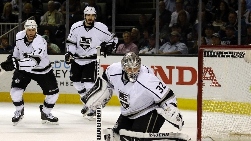 Los Angeles Kings goalie Jonathan Quick, right, watches a shot from the San Jose Sharks sail wide during the first period of Game 4 of an NHL hockey first-round Stanley Cup playoff series Wednesday, April 20, 2016, in San Jose, Calif. At left are Kings' Rob Scuderi (7) and Jake Muzzin (6). (AP Photo/Ben Margot)