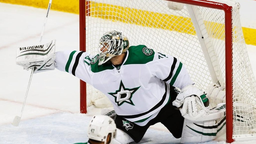 Dallas Stars goalie Antti Niemi of Finland deflects a shot during the first period of Game 4 in the first round of the NHL Stanley Cup hockey playoffs against the Minnesota Wild Wednesday, April 20, 2016, in St. Paul, Minn. (AP Photo/Jim Mone)