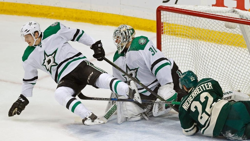 Dallas Stars' John Klingberg, left, of Sweden, left, is upended as he helped goalie Antti Niemi of Finland stop a scoring attempt by Minnesota Wild's Nino Niederreiter of Switzerland during the first period of Game 4 in the first round of the NHL Stanley Cup hockey playoffs Wednesday, April 20, 2016, in St. Paul, Minn. (AP Photo/Jim Mone)