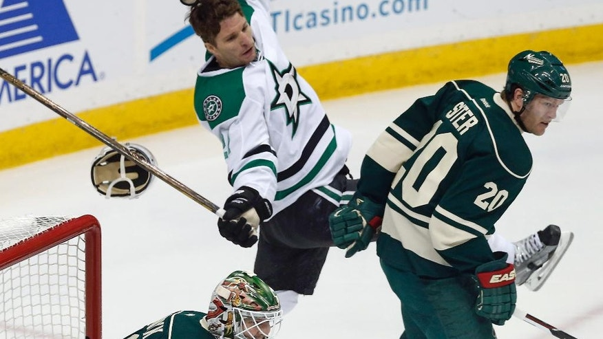 Dallas Stars' Antoine Roussel, left, of France, loses his helmet as he gets shoved by Minnesota Wild's Ryan Suter during the first period of Game 4 in the first round of the NHL Stanley Cup hockey playoffs Wednesday, April 20, 2016, in St. Paul, Minn. (AP Photo/Jim Mone)