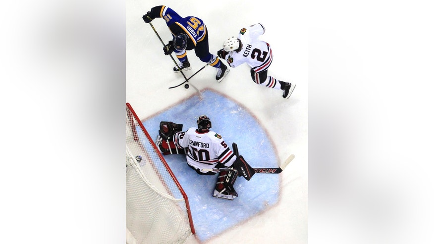 St. Louis Blues' Robby Fabbri, top left, tries to control the puck as Chicago Blackhawks goalie Corey Crawford, bottom, and Blackhawks' Duncan Keith defend during the second period in Game 5 of an NHL hockey first-round Stanley Cup playoff series Thursday, April 21, 2016, in St. Louis. (AP Photo/Jeff Roberson)