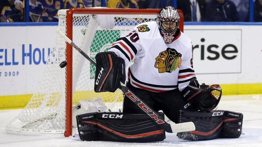 Chicago Blackhawks goalie Corey Crawford deflects a puck during the second period in Game 5 of an NHL hockey first-round Stanley Cup playoff series against the St. Louis Blues on Thursday, April 21, 2016, in St. Louis. (AP Photo/Jeff Roberson)