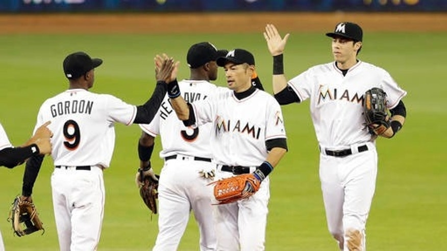 Miami Marlins right fielder Ichiro Suzuki, right foreground, gives a high-five to teammate Dee Gordon (9) after a baseball game against the Washington Nationals, Thursday, April 21, 2016, in Miami. The Marlins won 5-1. (AP Photo/Alan Diaz)