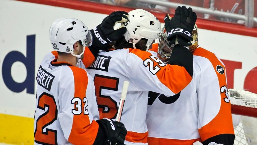 Philadelphia Flyers defenseman Mark Streit (32), from Switzerland; center Ryan White (25) and goalie Michal Neuvirth (30), from the Czech Republic, celebrate after Game 5 in the first round of the NHL Stanley Cup hockey playoffs against the Washington Capitals, Friday, April 22, 2016, in Washington. The Flyers won 2-0. (AP Photo/Alex Brandon)