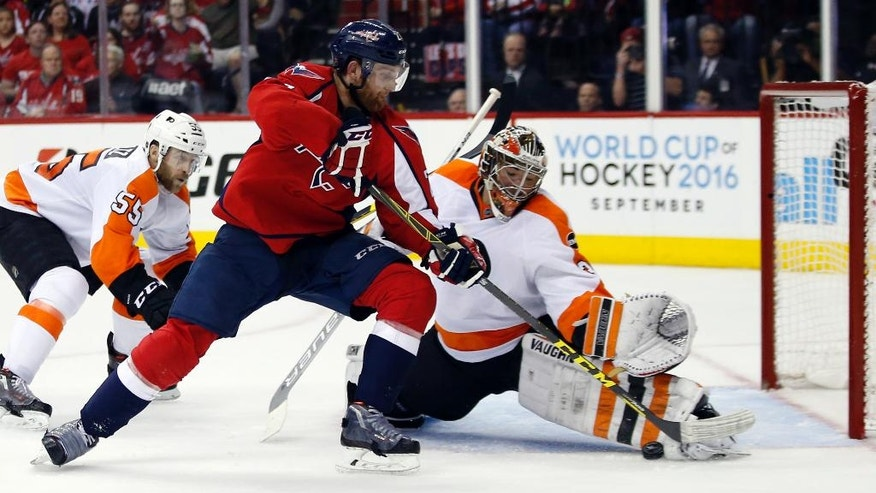 Washington Capitals defenseman Karl Alzner (27) can't score past Philadelphia Flyers goalie Michal Neuvirth (30), from the Czech Republic, during the second period of Game 5 in a first-round NHL Stanley Cup hockey playoff series, Friday, April 22, 2016, in Washington. (AP Photo/Alex Brandon)