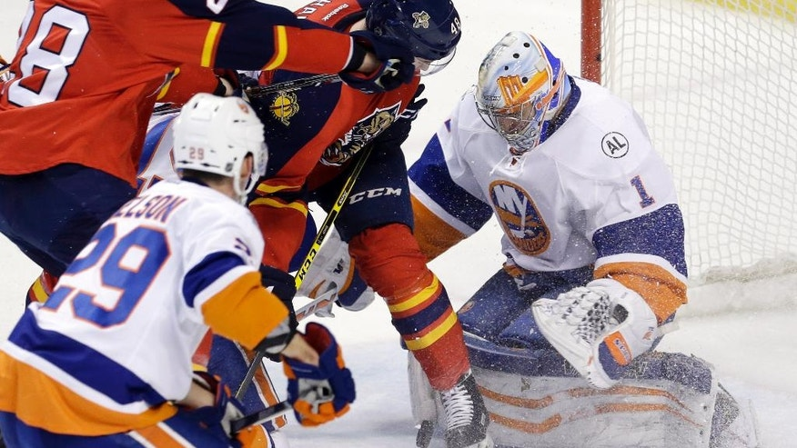 New York Islanders goalie Thomas Greiss (1) stops a shot as he defends against Florida Panthers left wing Garrett Wilson (28) and Logan Shaw (48) during the second period of Game 5 of an NHL hockey first-round Stanley Cup playoff series, Friday, April 22, 2016, in Sunrise, Fla. (AP Photo/Alan Diaz)