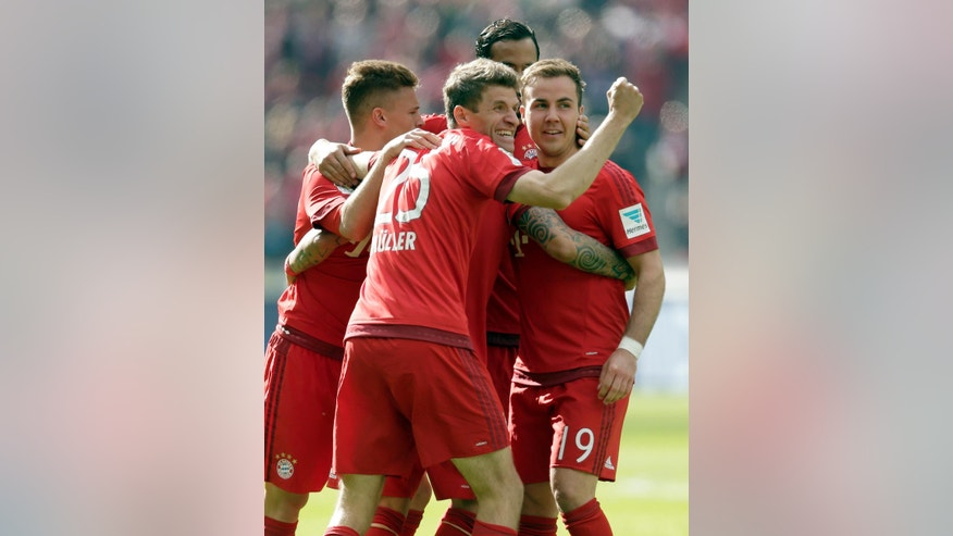 Bayern's Thomas Mueller, center, and his teammates celebrate after Arturo Vidal scored the opening goal during the German Bundesliga soccer match between Hertha BSC Berlin and FC Bayern Munich in Berlin, Germany, Saturday, April 23, 2016. (AP Photo/Michael Sohn)