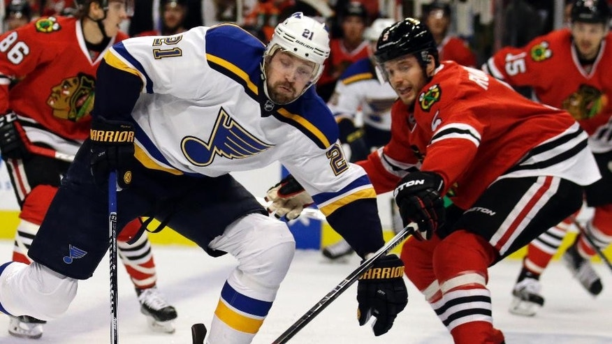 St. Louis Blues center Patrik Berglund, left, controls the puck against Chicago Blackhawks defenseman David Rundblad during the first period in Game 6 of an NHL hockey first-round Stanley Cup playoff series Saturday, April 23, 2016, in Chicago. (AP Photo/Nam Y. Huh)