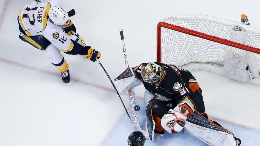 Anaheim Ducks goalie Frederik Andersen, right, blocks a shot by Nashville Predators center Mike Fisher during the first period of Game 5 in an NHL hockey Stanley Cup playoffs first-round series in Anaheim, Calif., Saturday, April 23, 2016. (AP Photo/Chris Carlson)