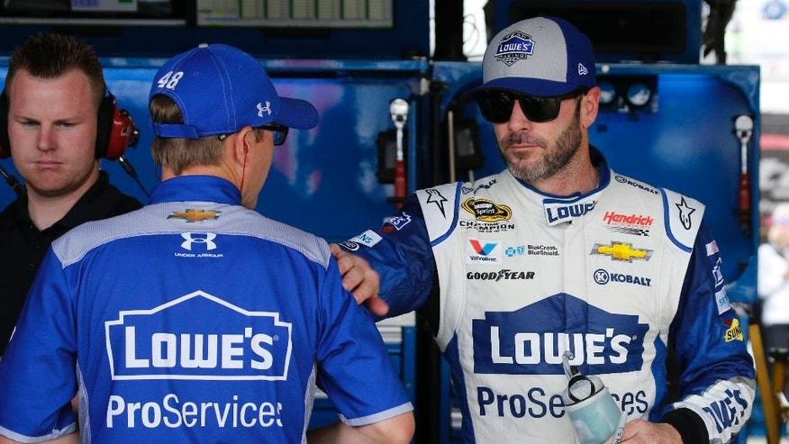 Jimmie Johnson, right, greets a crew member in the garage after practice for Sunday's NASCAR Sprint Cup auto race at Richmond International Raceway in Richmond, Va., Saturday, April 23, 2016. (AP Photo/Steve Helber)