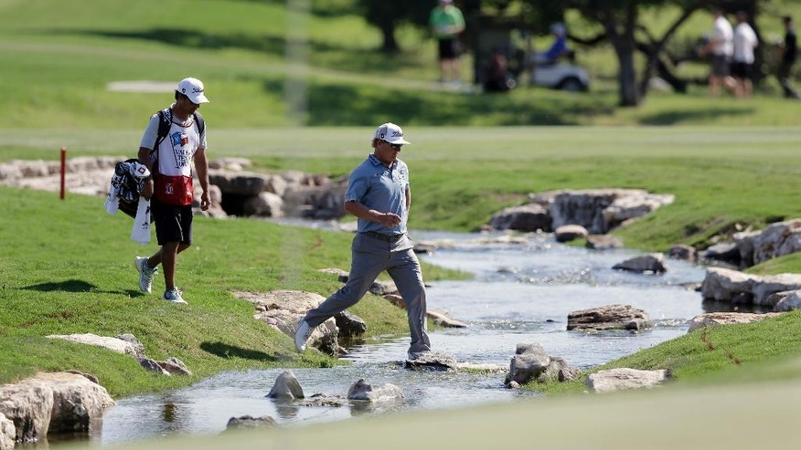 Charley Hoffman, right, crosses a creek on the 18th hole during the third round of the Texas Open golf tournament, Saturday, April 23, 2016, in San Antonio. (AP Photo/Eric Gay)