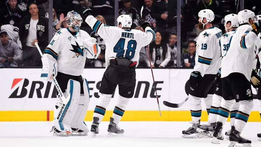 San Jose Sharks goalie Martin Jones, left, celebrates with center Tomas Hertl, center, of the Czech Republic, and other teammates after Game 5 in an NHL hockey Stanley Cup playoffs first-round series against the Los Angeles Kings, Friday, April 22, 2016, in Los Angeles. The Sharks won 6-3 and took the series. (AP Photo/Mark J. Terrill)
