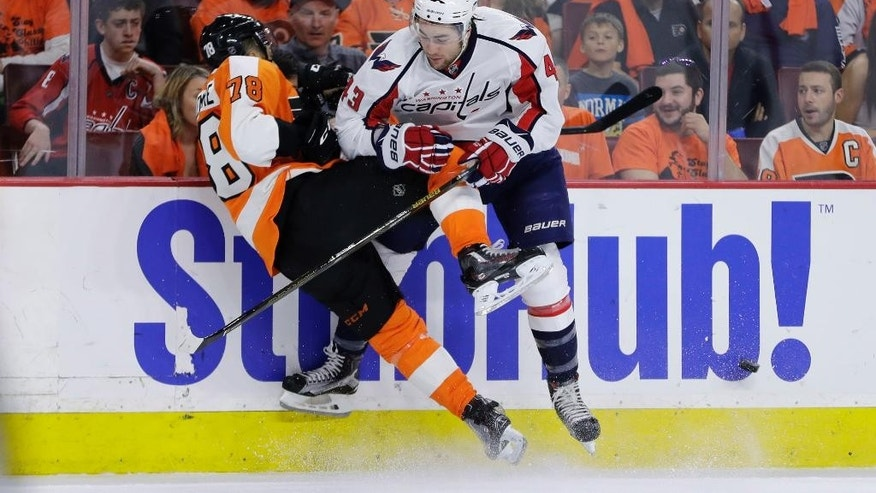 Washington Capitals' Tom Wilson, right, checks Philadelphia Flyers' Pierre-Edouard Bellemare during the first period of Game 6 in the first round of the NHL Stanley Cup hockey playoffs, Sunday, April 24, 2016, in Philadelphia. (AP Photo/Matt Slocum)