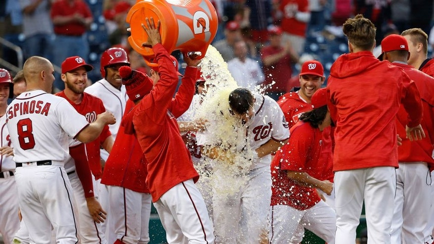 Apr 24, 2016; Washington, DC, USA; Washington Nationals center fielder Chris Heisey (14) gets a bucket of Gatorade dumped on him by teammates after hitting a walk-off home run against the Minnesota Twins in the sixteenth inning at Nationals Park. The National won 5-4 in sixteen innings. Mandatory Credit: Geoff Burke-USA TODAY Sports