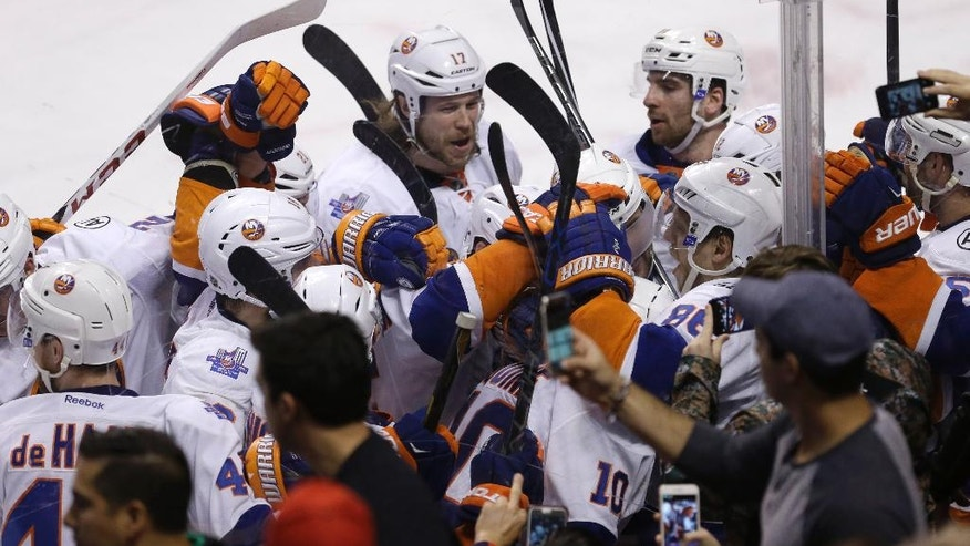 New York Islanders celebrate with Alan Quine (10) after he scored in the second overtime against the Florida Panthers during Game 5 of an NHL hockey first-round Stanley Cup playoff series, early Saturday, April 23, 2016, in Sunrise, Fla. The Islanders won 2-1. (AP Photo/Alan Diaz)