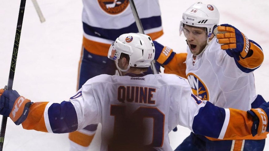 New York Islanders left wing Nikolay Kulemin (86) celebrates with Alan Quine (10) after Quine scored the game-winning goal against the Florida Panthers during the second overtime period of Game 5 of an NHL hockey first-round Stanley Cup playoff series, early Saturday, April 23, 2016, in Sunrise, Fla. The Islanders won 2-1. (AP Photo/Alan Diaz)