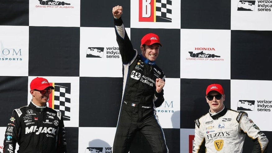 Simon Pagenaud, of France, center, cheers his first place win on the podium with Graham Rahal of New Albany, Ohio, left, in second place and Josef Newgarden, of Hendersonville, Tenn., right, in third place after the Indy Grand Prix of Alabama auto race, Sunday, April 24, 2016, in Birmingham, Ala. (AP Photo/Brynn Anderson)