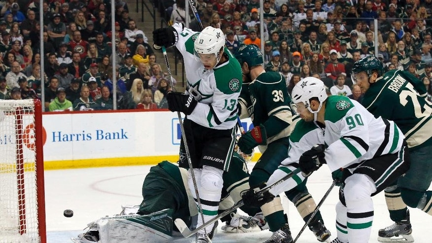 Dallas Stars center Jason Spezza (90) scores on Minnesota Wild goalie Devan Dubnyk past Stars teammate Mattias Janmark (13) during the first period of Game 6 in the first round of the NHL Stanley Cup hockey playoffs in St. Paul, Minn., Sunday, April 24, 2016. (AP Photo/Ann Heisenfelt)
