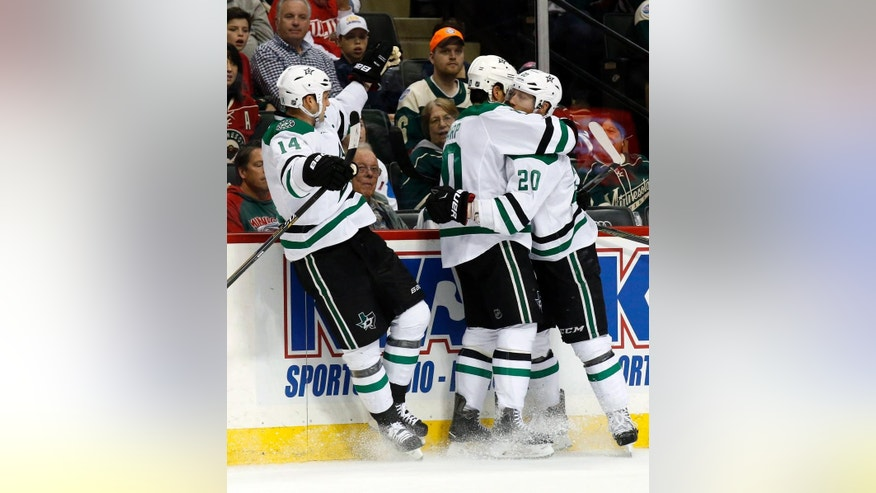 Dallas Stars left wing Patrick Sharp, center, celebrates with teammates  Cody Eakin (20) and Jamie Benn (14) after scoring on Minnesota Wild goalie Devan Dubnyk during the first period of Game 6 in the first round of the NHL Stanley Cup hockey playoffs in St. Paul, Minn., Sunday, April 24, 2016. (AP Photo/Ann Heisenfelt)
