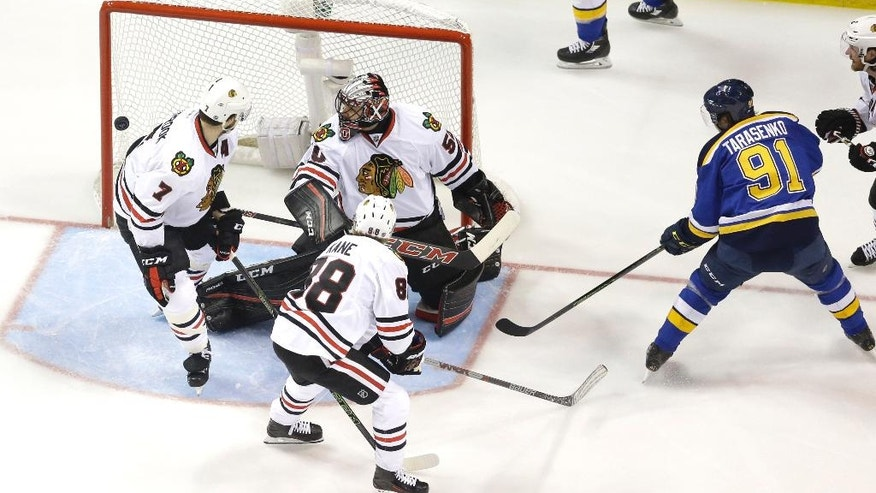 St. Louis Blues' Vladimir Tarasenko (91), of Russia, watches as a puck slips past Chicago Blackhawks goalie Corey Crawford, Brent Seabrook (7) and Patrick Kane (88) during the first period in Game 7 of an NHL hockey first-round Stanley Cup playoff series Monday, April 25, 2016, in St. Louis. (AP Photo/Jeff Roberson)