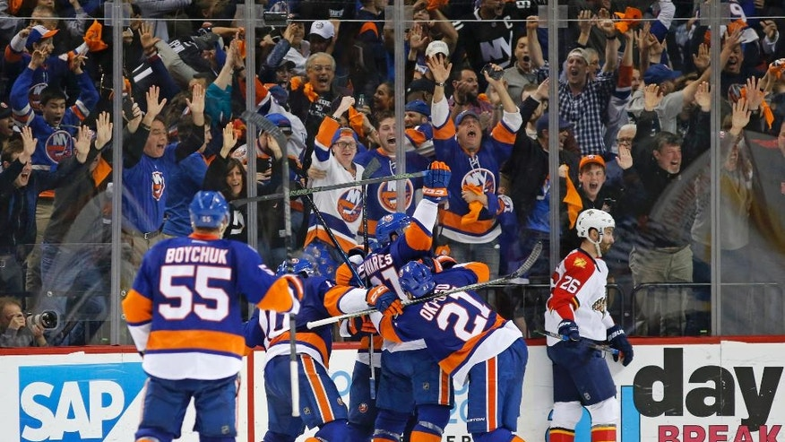 Fans react as teammates celebrate with New York Islanders center John Tavares (91) who scored the winning goal in second overtime in Game 6 of an NHL hockey first-round Stanley Cup playoff series against the Florida Panthers in New York, Sunday, April 24, 2016. Florida Panthers right wing Teddy Purcell (26), right, skates off the ice. (AP Photo/Kathy Willens)