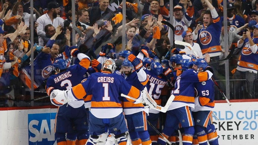 Fans react as New York Islanders celebrate eliminating the Florida Panthers 2-1 in second overtime period in Game 6 of an NHL hockey first-round Stanley Cup playoff series in New York, Sunday, April 24, 2016. (AP Photo/Kathy Willens)