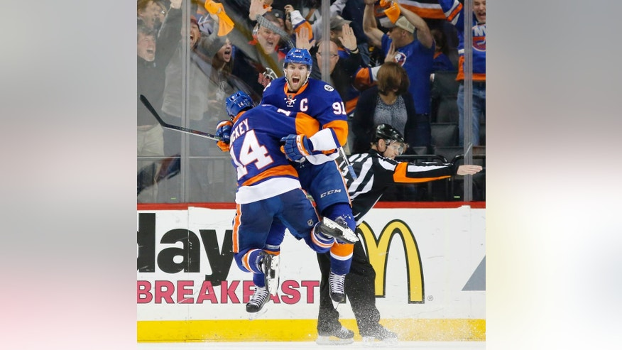 New York Islanders defenseman Thomas Hickey (14) leaps in the air with New York Islanders center John Tavares (91) after Tavares scored the winning goal in the second overtime period of Game 6 of an NHL hockey first-round Stanley Cup playoff series against the Florida Panthers in New York, Sunday, April 24, 2016. The Islanders defeated the 2-1. (AP Photo/Kathy Willens)