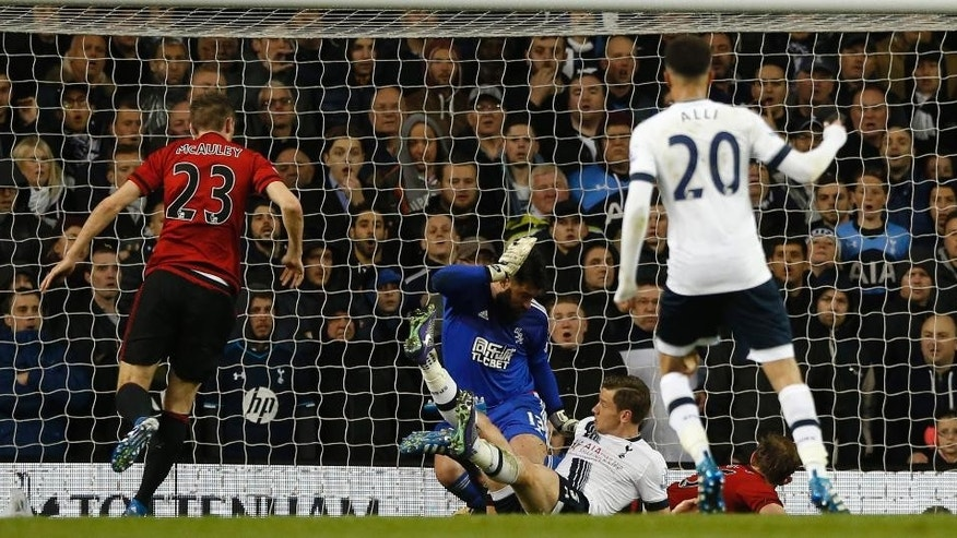 West Brom's Craig Dawson, on the ground right, scores an own goal through West Brom's goalkeeper Boaz Myhill legs as Tottenham Hotspur's Jan Vertonghen falls during their English Premier League soccer match between Tottenham Hotspur and West Bromwich Albion at White Hart Lane in London, Monday, April, 25,  2016. (AP Photo/Alastair Grant)
