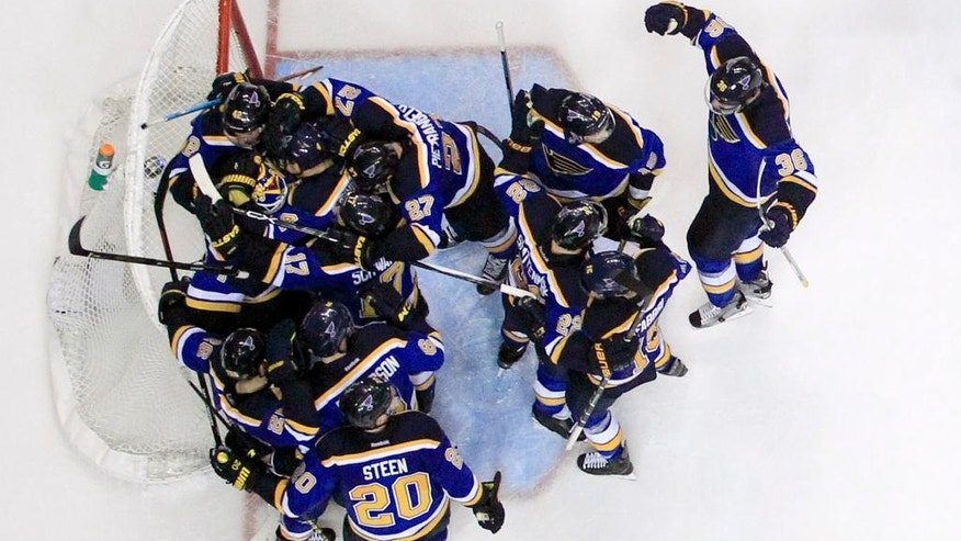 Members of the St. Louis Blues gather around goalie Brian Elliott following the Blues' 4-3 victory over the Chicago Blackhawks in Game 7 of an NHL hockey first-round Stanley Cup playoff series Monday, April 25, 2016, in St. Louis. The Blues won the series 4-3. (AP Photo/Jeff Roberson)