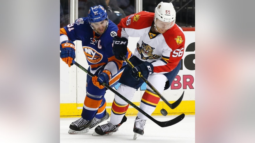 New York Islanders center John Tavares (91) tries to get the puck from Florida Panthers defenseman Michael Matheson (56) in the second period of Game 6 of an NHL hockey first-round Stanley Cup playoff series in New York, Sunday, April 24, 2016. (AP Photo/Kathy Willens)
