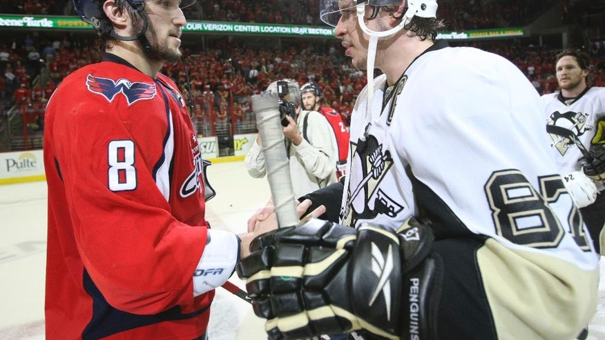 FILE - In this March 13, 2009 file photo, Washington Capitals' Alex Ovechkin (8), from Russia, shakes hands with Pittsburgh Penguins' Sidney Crosby (87) following Game 7 of an NHL hockey second-round playoff series, in Washington. After dispatching the New York Rangers in five games, Pittsburgh faces top-seed Washington in the second round, their ninth postseason clash but the first since 2009. (AP Photo/Bruce Bennett, Pool, File)