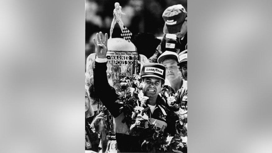 FILE - In this May 24, 1987 file photo, Al Unser raises four fingers in front of the Borg-Warner trophy after winning his fourth Indianapolis 500 auto race at Indianapolis Motor Speedway in Indianapolis, Ind. (AP Photo/Mike Conroy)