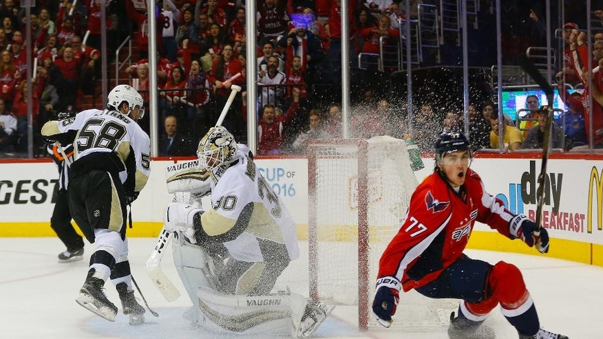 Washington Capitals right wing T.J. Oshie (77) starts to celebrate his goal against Pittsburgh Penguins goalie Matt Murray (30) and Kris Letang (58) during the second period of Game 1 in an NHL hockey Stanley Cup Eastern Conference semifinals Thursday, April 28, 2016 in Washington. (AP Photo/Pablo Martinez Monsivais)