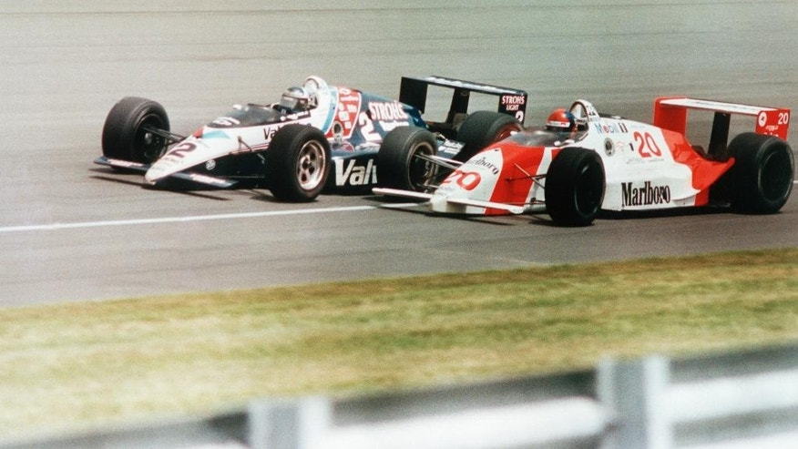 FILE - In this May 28, 1989 file photo, Emerson Fittipaldi, right, bumps the car driven by AI Unser, Jr. with less than two laps to go in the 73rd running of the Indianapolis 500 auto race in Indianapolis.   (AP Photo/Larry Drake)