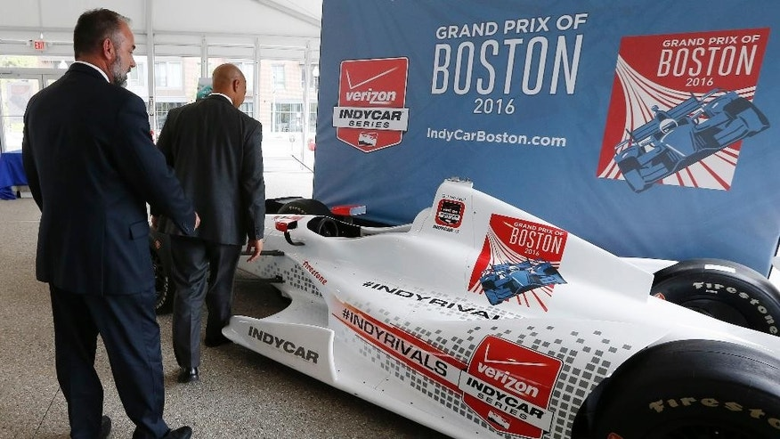 FILE - In this May 21, 2015, file photo, City of Boston chief of economic development John Barros, right, and tourism, sports and entertainment director Ken Brissette, left, examine an IndyCar mockup following a news conference in Boston announcing the inaugural Grand Prix of Boston scheduled for 2016. Organizers of the race, which had been planned for Labor Day weekend this year and again each year through 2020, told the open wheel circuit Friday, April 29, 2016, that they have scratched plans to bring a race to the city. (AP Photo/Michael Dwyer, File)