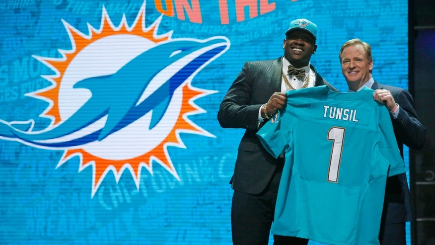 Mississippi's Laremy Tunsil poses for photos with NFL commissioner Roger Goodell after being selected by the Miami Dolphins as the 13th pick in the first round of the 2016 NFL football draft, Thursday, April 28, 2016, in Chicago.