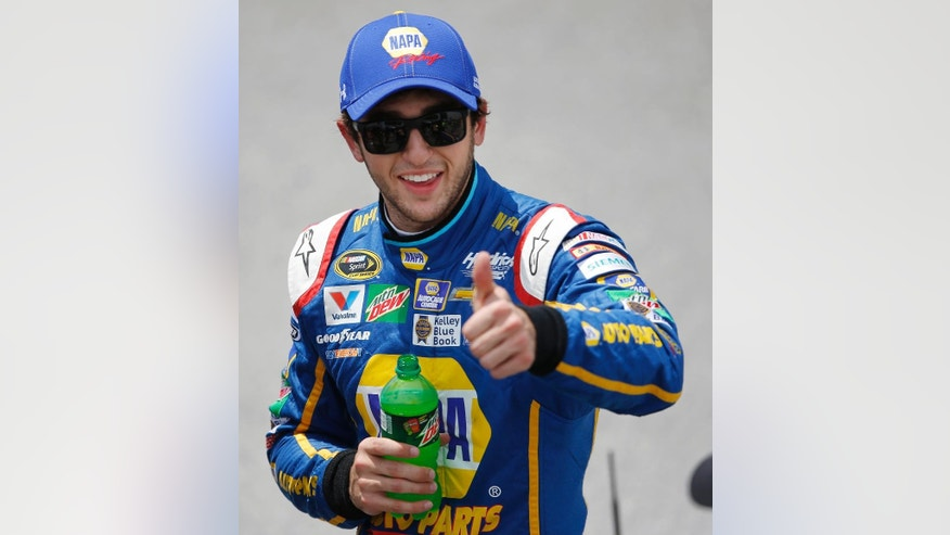 NASCAR driver Chase Elliott gives a thumbs up to Sprint Cup Series driver Dale Earnhardt Jr. after qualifying first for Sunday's NASCAR auto race at Talladega Superspeedway, Saturday, April 30, 2016, in Talladega, Ala. (AP Photo/John Bazemore)