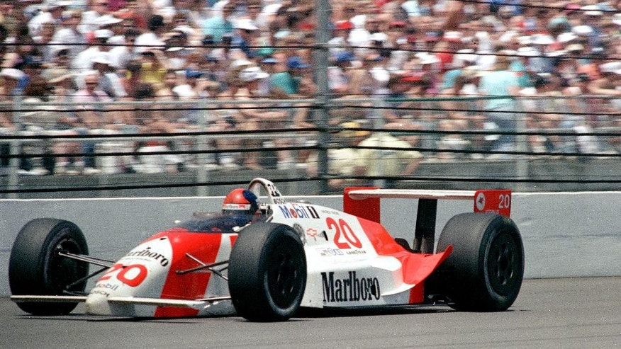 FILE - In this May 27, 1990 file photo, Arie Luyendyk waves to the crowd after winning the 74th running of the Indianapolis 500 auto race at Indianapolis Motor Speedway. (AP Photo/Mark Duncan, File)