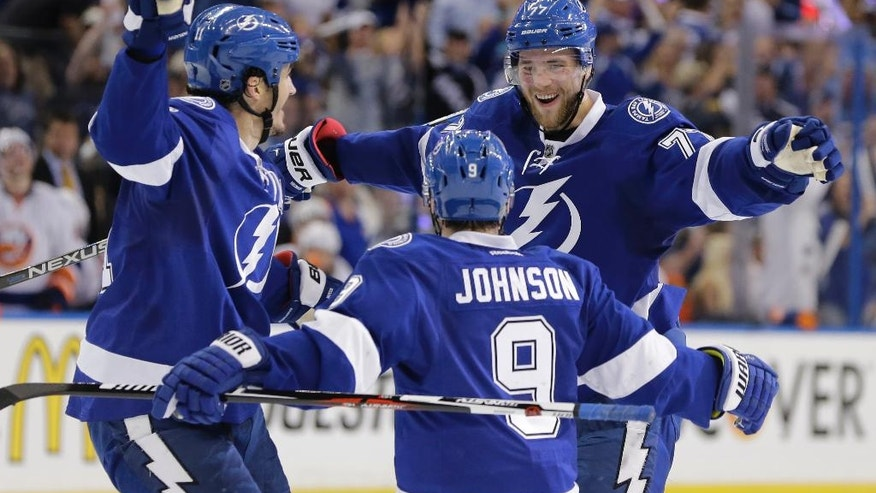 Tampa Bay Lightning defenseman Victor Hedman (77), of Sweden, is congratulated by centers Tyler Johnson (9) and Brian Boyle (11) after scoring a goal during the second period of Game 2 of the NHL hockey Stanley Cup Eastern Conference semifinals against the New York Islanders,  Saturday, April 30, 2016, in Tampa, Fla. Johnson was credited with the assist. (AP Photo/Chris O'Meara)