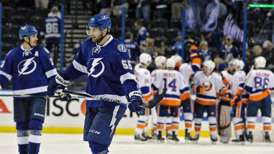 Tampa Bay Lightning center Brian Boyle (11) and defenseman Braydon Coburn (55) skate off as the New York Islanders celebrate a 5-3 win during Game 1 of the NHL hockey Stanley Cup Eastern Conference semifinals Wednesday, April 27, 2016, in Tampa, Fla. (AP Photo/Chris O'Meara)
