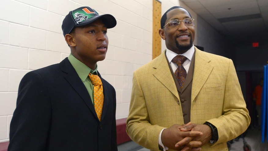 FILE - In this Feb. 6, 2013, file photo, Ray Anthony Lewis III, left, and his father, former Baltimore Ravens linebacker Ray Lewis Jr., chat after his national signing day ceremony in the Lake Mary Prep auditorium in Lake Mary, Fla.