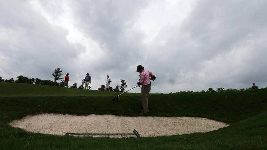 Storm clouds loom as grounds crew groom the 18th hole before the start of the third round of the PGA Zurich Classic golf tournament at TPC Louisiana in Avondale, La., Saturday, April 30, 2016. (AP Photo/Gerald Herbert)