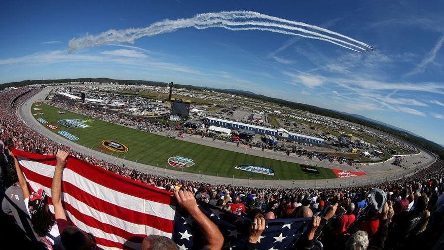 TALLADEGA, AL - OCTOBER 19: Fans hold up an American flag during the flyover peior to the NASCAR Sprint Cup Series GEICO 500 at Talladega Superspeedway on October 19, 2014 in Talladega, Alabama. (Photo by Todd Warshaw/Getty Images)