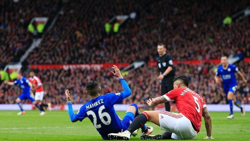 Leicester's Riyad Mahrez, centre left, appeals for a penalty after a tackle by Manchester United's Marcos Rojo during the English Premier League soccer match between Manchester United and Leicester at Old Trafford Stadium, Manchester, England, Sunday, May 1, 2016. (AP Photo/Jon Super)